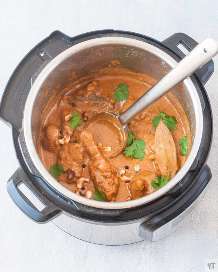 chicken korma in an instant pot with coriander leaves and cashews as garnish
