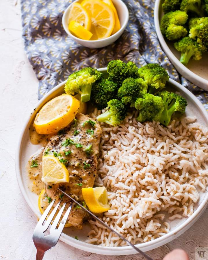 instant pot lemon garlic chicken on a white plate with a garnish of lemon slices and parsley on a bed of brown rice and steamed broccoli