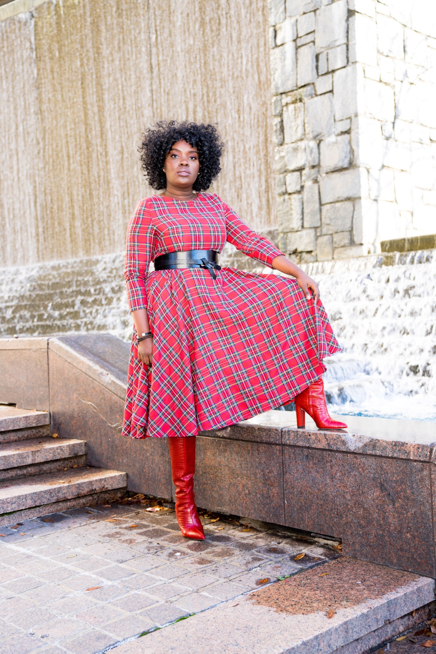 Black woman wearing thrift tartan dress by water fountain.