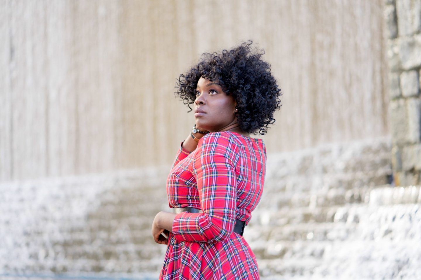 Curly haired black girl wearing red tartan dress