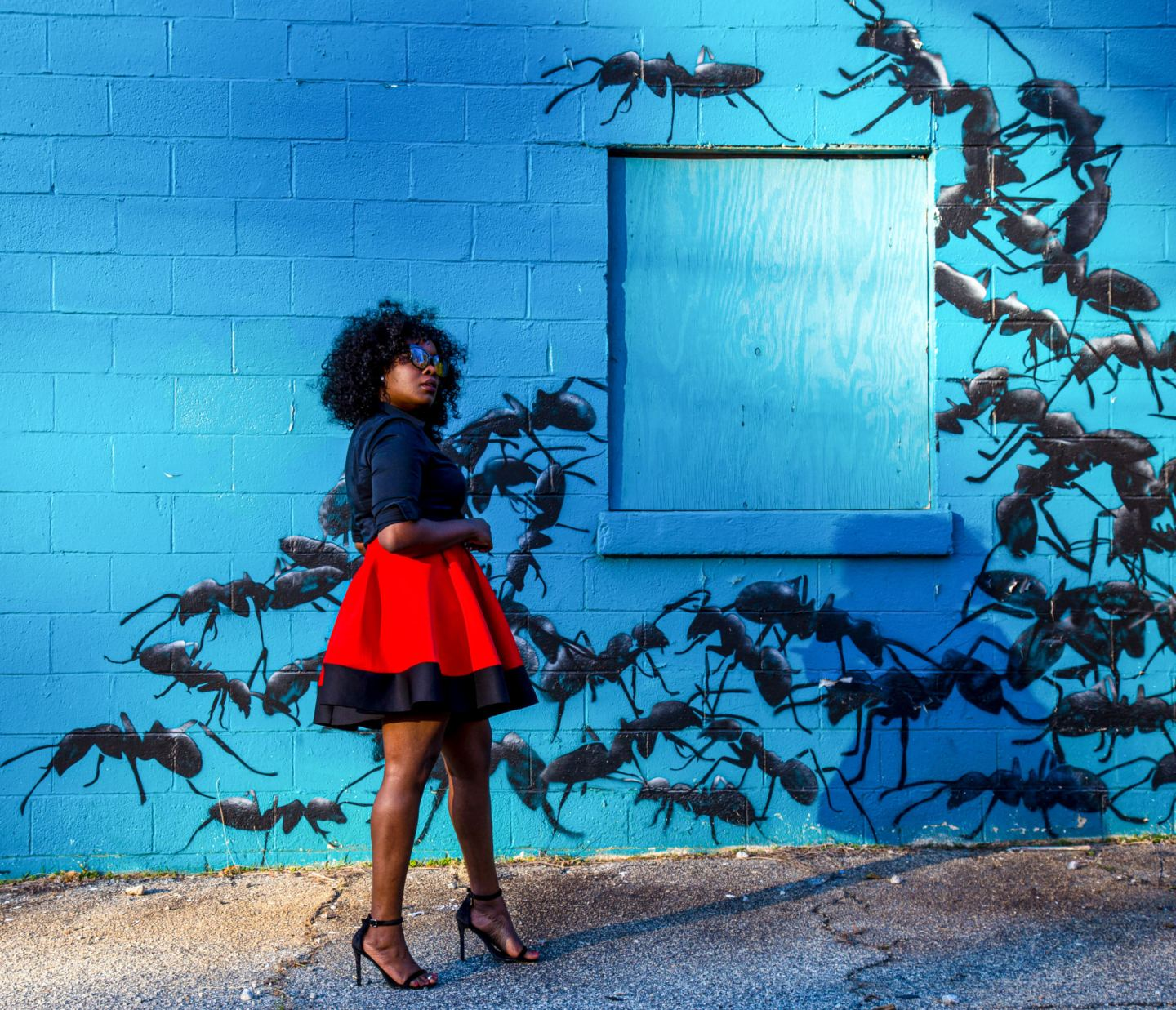 ChiChi standing in front of an ant mural wall wearing a red neoprene circle skirt