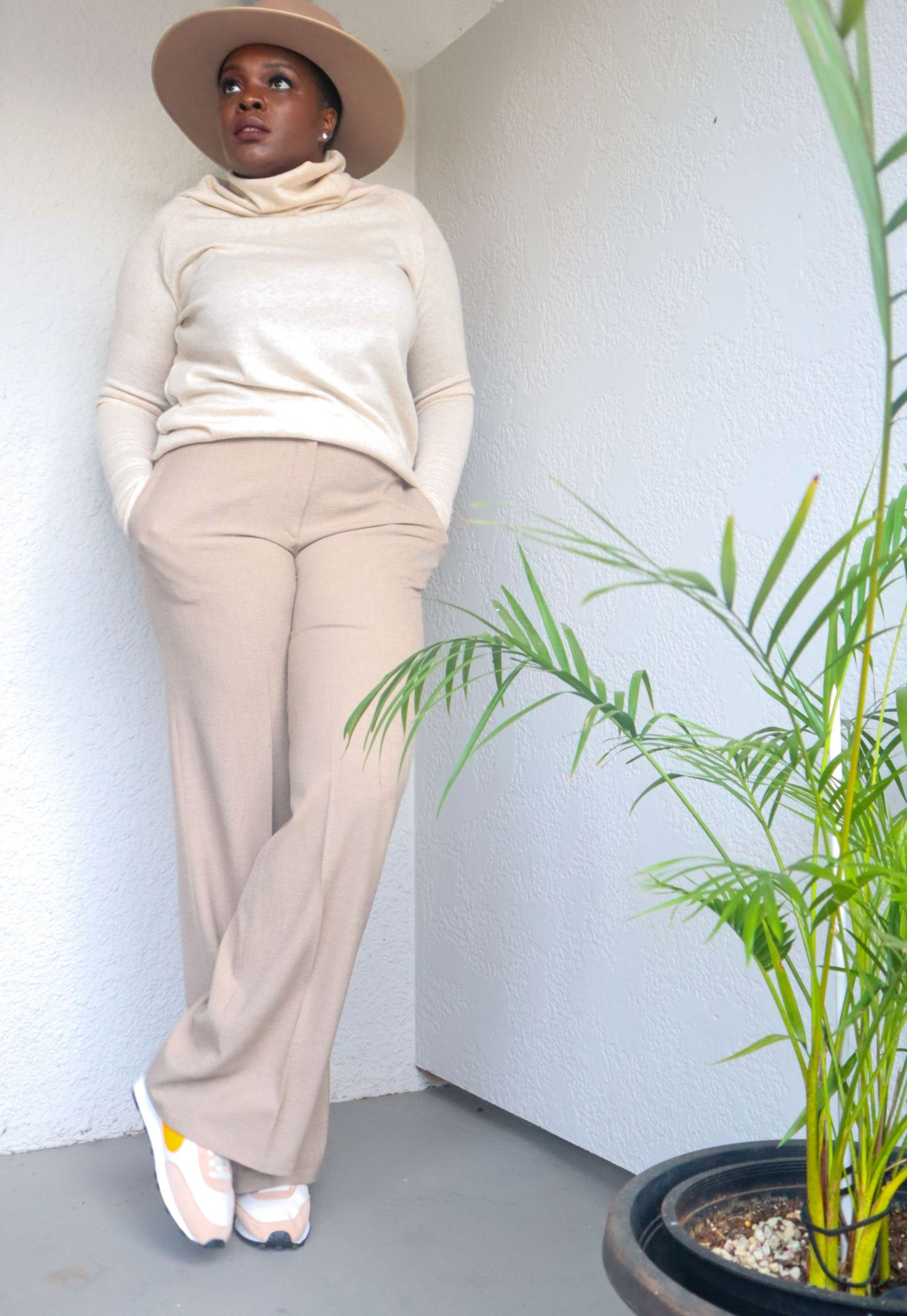 Neutrals on neutrals long sleeve cashmere sweater and trousers by a palm plant.