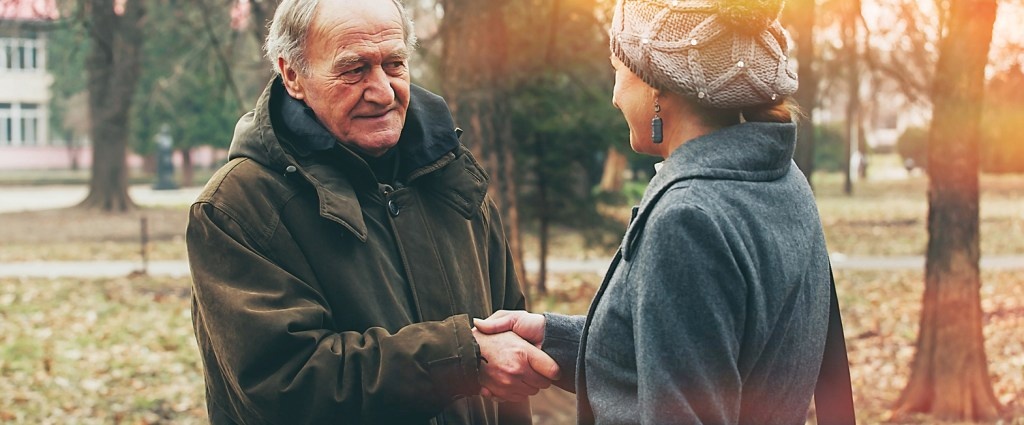 Older man and woman shaking hands in a park