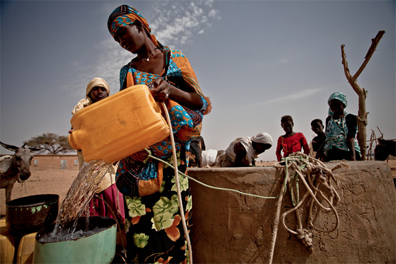 Refilling water container. Photo by Oxfam.