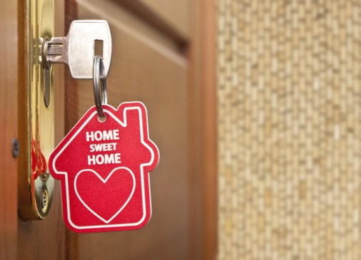 "Key in lock with ""Home Sweet Home"" keychain. Photo by Shutterstock."