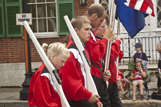 family color guard in red shirts and white wooden rifles
