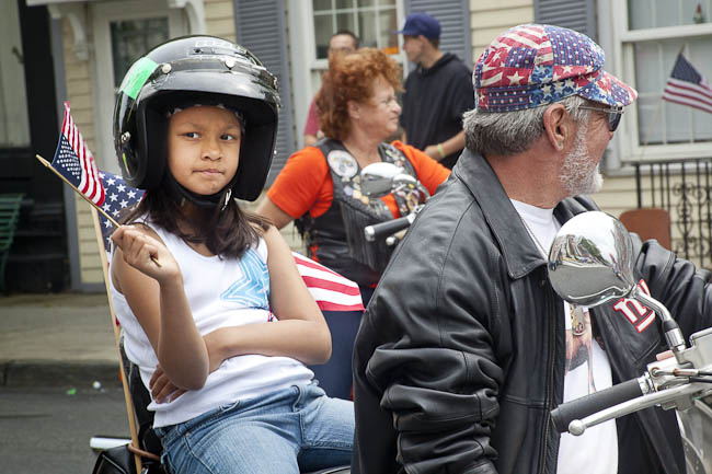 father and daughter wearing helment with Irish flag  waving US flag on back of motorcycle
