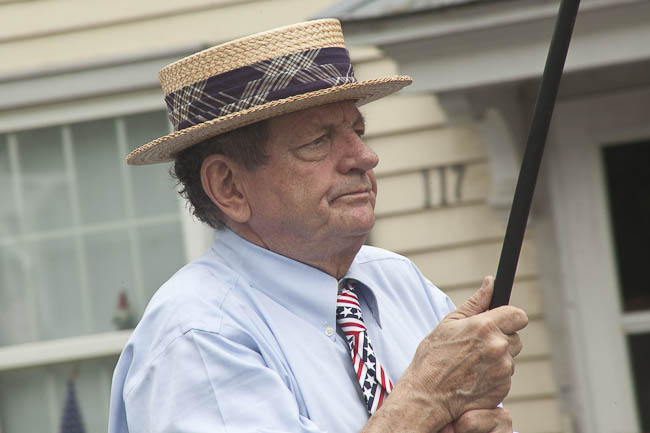 man in straw hat holding flag pole