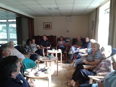 People sitting in a lounge listening to a fire safety talk at Carrs Lane Gardens