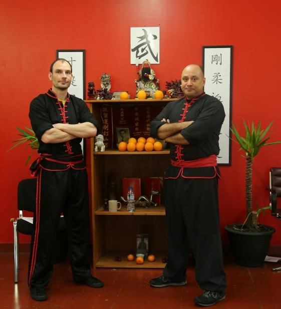 Si-Tai-Gung Pedro Cepero Yee and Sifu Simon Hepple stand in front of the altar at the European headquaters in Aberdeen.