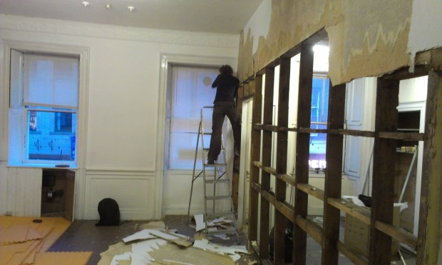 Student Jenn lending a hand to take a partition wall down .
