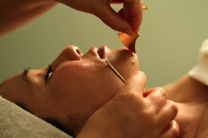 Small, gold-colored tools are used to scrape and stimulate a relaxed client's face in a unique massage.