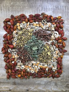 A geometric arrangement of dried fruits and other herbs used to treat acne.