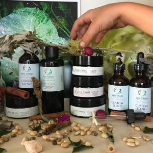 A young person's hand places dried herbs over a collection of Yin Yang Dermatology jars and bottles.