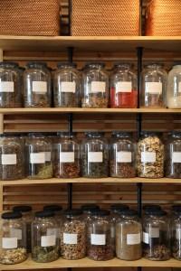 Jars of herbs line the shelves.