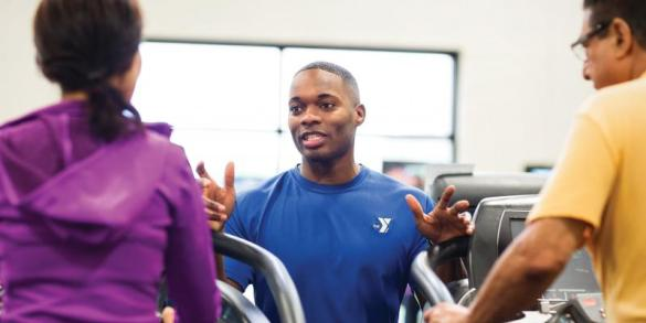 YMCA of WNC Personal Training YMCA Western North Carolina personal trainer consults a male and female client  each standing on  treadmills