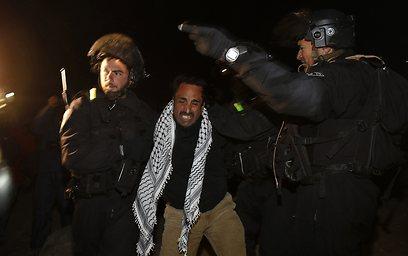 אחד הפלסטינים מורחק מהמקום (צילום: רויטרס)