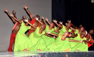 Group of Jamaican dancers leaning with arms stretched looking to top left of frame, women dressed in bright green dresses and men in red pants and vests