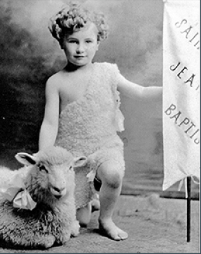 """The black-and-white photo depicts a boy representing petit St. Jean-Baptiste, a national saint, with a lamb to his right and a flag that reads """"Saint Jean Baptiste"""" to his left."""