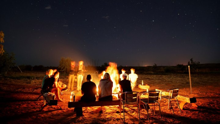 Photograph of people seated around a campfire telling stories at night