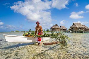 A native Polynesian walks a traditional raft through shallow water.
