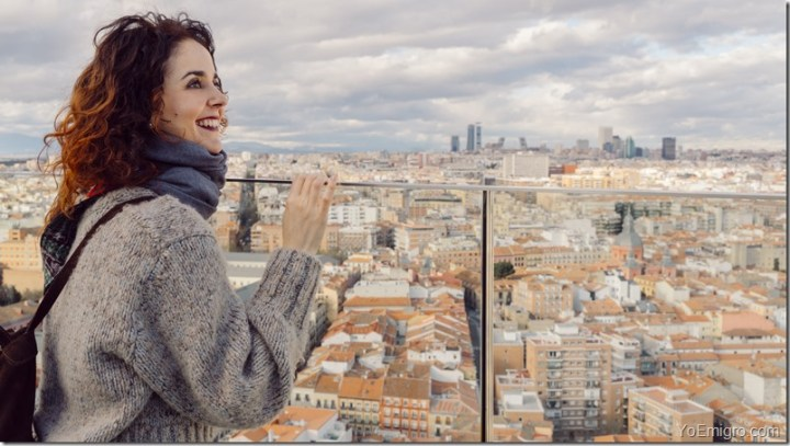 European woman on holidays discovering culture, tourism and spanish lifestyle. Tourist female sightseeing Madrid skyline and rooftops from a high view hotel terrace.