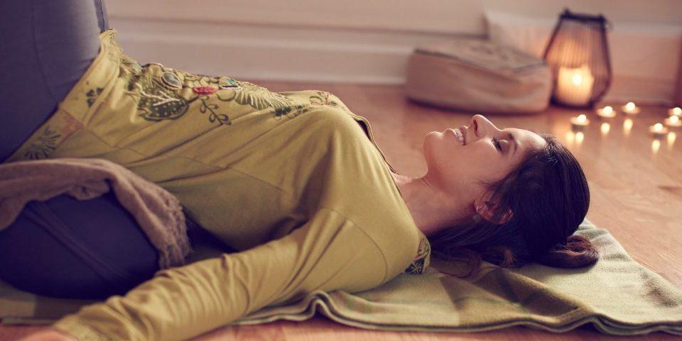Image qui montre une femme allongee sur le dos avec un bolster sous les hanches et les jambes allongees contre le mur vers le plafond dans une ambiance relaxante avec des bougies