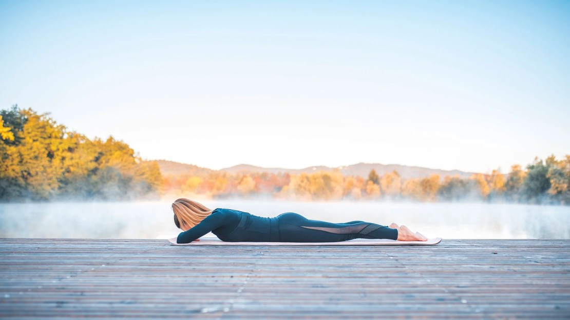 A woman demonstrates crocodile pose while lying on a deck with mountains