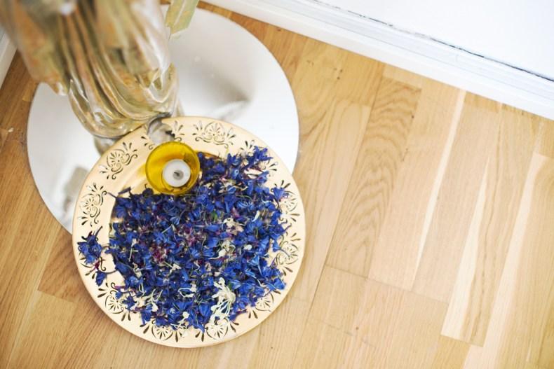 Halv guldstaty med blå blommor och ett ljus på ett fat
