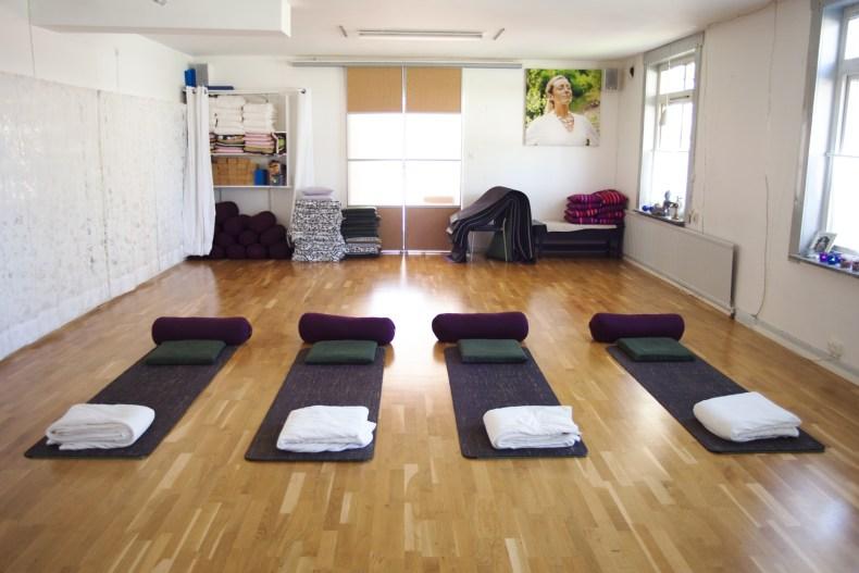 Mattor med kuddar, bolster och filtar på golvet på Yogakällan