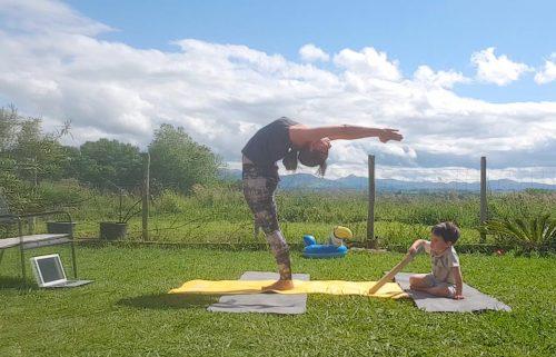 yoga avec enfant qui joue à côté de sa mère en backbend