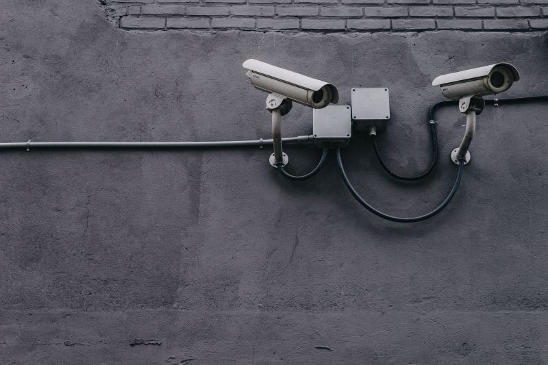 Two security cameras look pointedly at something