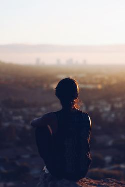 A young woman looks at something difficult to see in the distance, deep in thought.