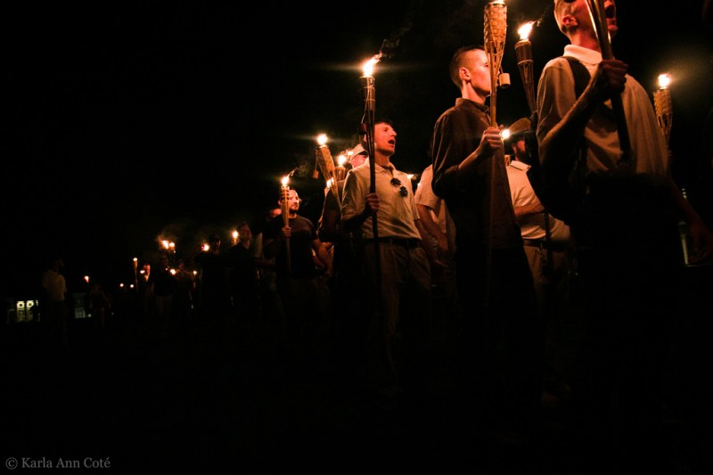 White supremacists line up in the night holding glowing tiki torches