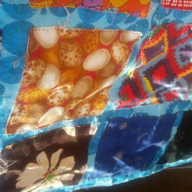 Four quilt squares in bright colors lit by sunlight: dark blue with silver stars and moons; white and beige eggs on a red background; a diamond pattern in red, blue, yellow, and orange; and a white flower on a brown background. The squares are surrounded by a bright blue trim.