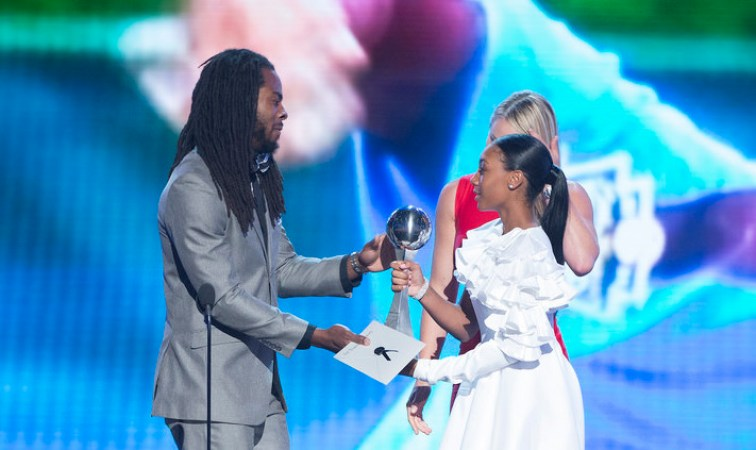 A man of color hands a large trophy to a young woman of color at an awards show.