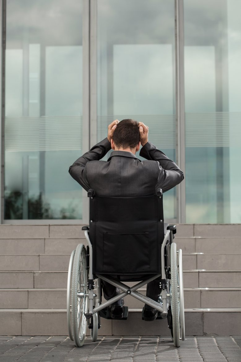 A man sits in his wheel chair at the bottom of a flight of stairs, looking exasperated at the lack of ramp.
