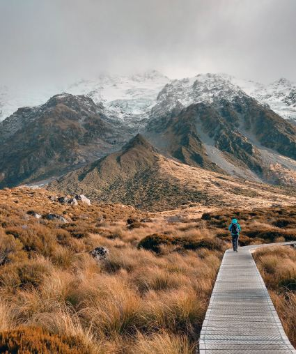 A person walks along the very beginning of a trail that will eventually lead to the top of a tall mountain. They have a long trip ahead of them.