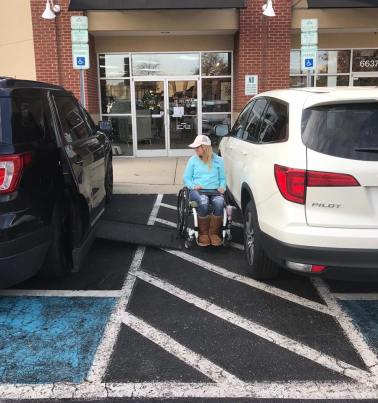 A woman in a wheel chair is blocked from getting into her car, due to another car parking over the striped lines.