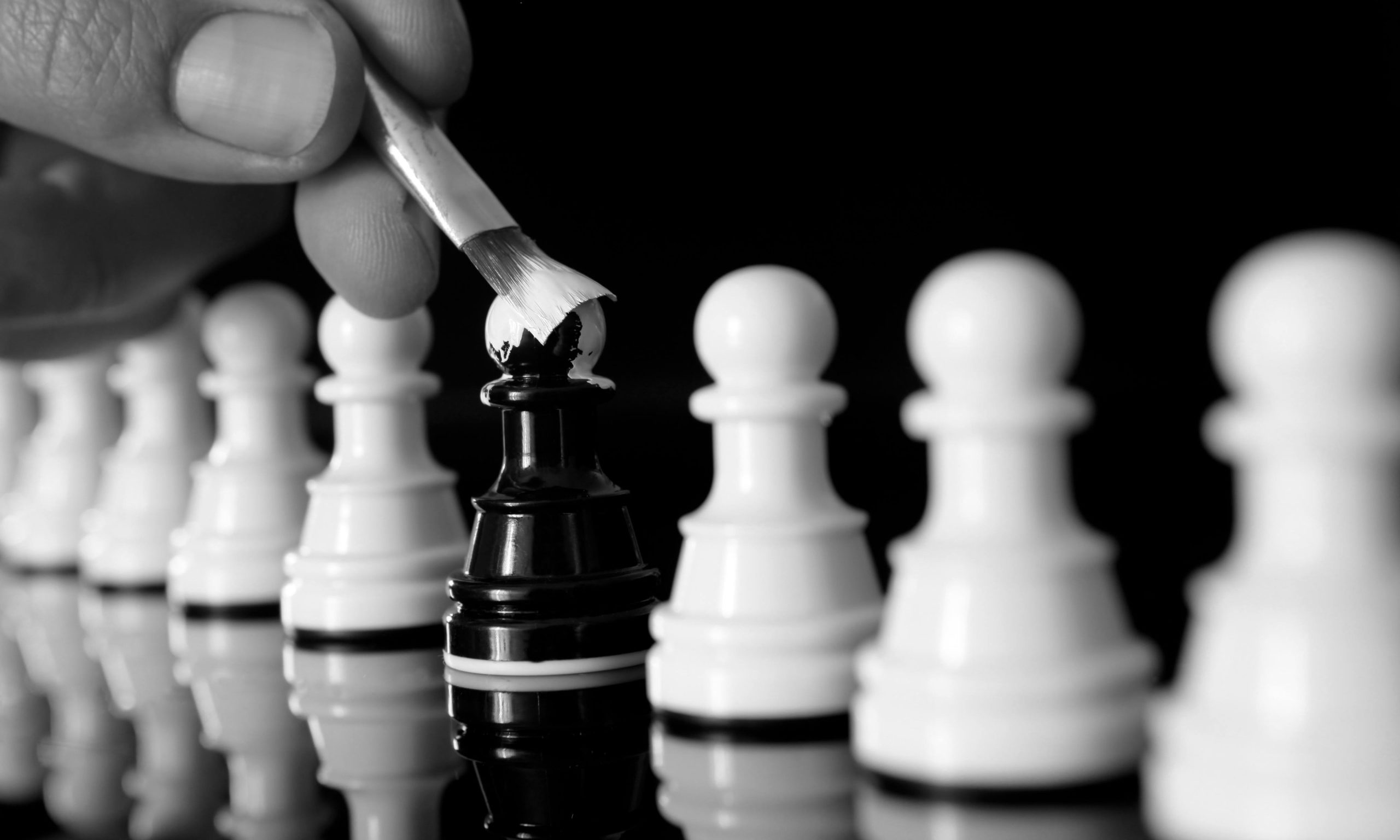 Amidst a line of uniformly white chess pieces, a single black chess piece is carefully painted white.