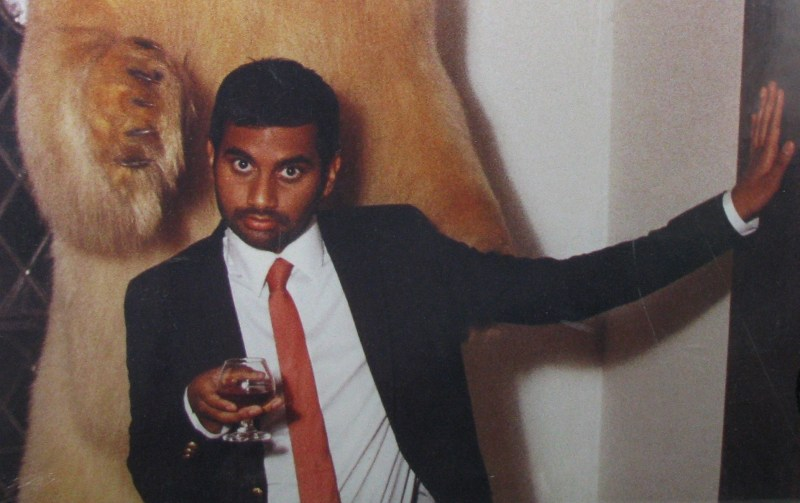 Aziz Ansari poses for a photo, looking sassy and holding a glass of red wine.