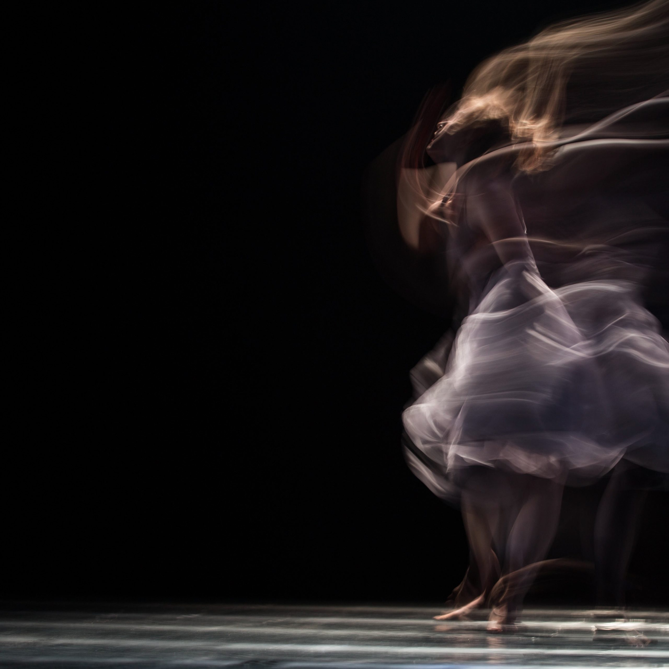 A dancer moves on a black empty stage, but her image is blurred, as if she