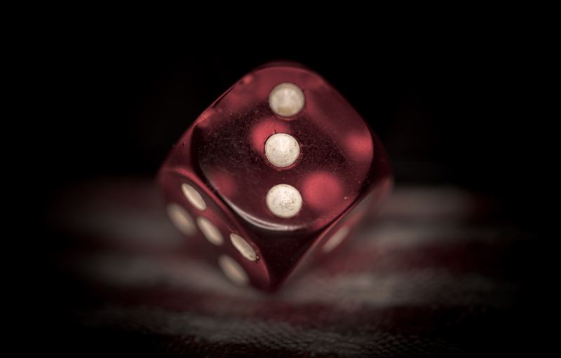A red 6-sided die sits on its corner as if suspended, not settling on any of the 6 sides.