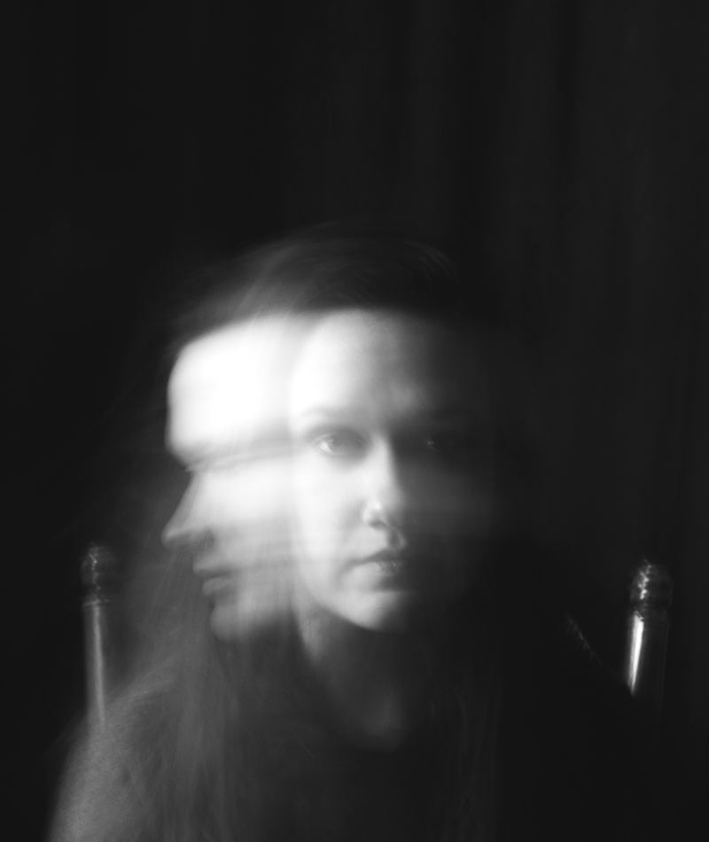 A woman stares somberly at the camera and then moves her head to the side mid-photo so that both figures look ghostly and transparent.
