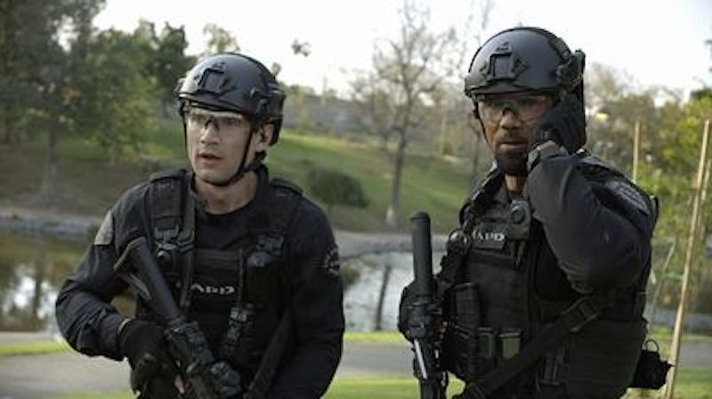 Two leading characters from the TV show SWAT dressed in full black riot gear, a river and grassy hill behind them.