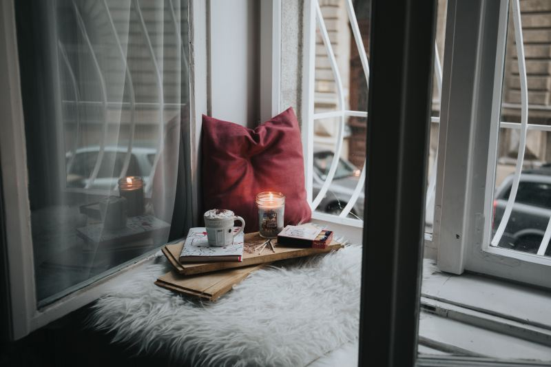 A cozy corner shows someone's self care rituals all lined up: a pillow, a fuzzy blanket, a candle and some incense, a book, and a mug full of hot chocolate.