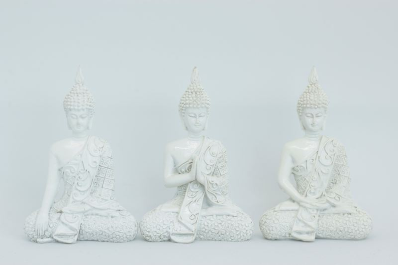 Three white Gautama Buddha figurines sitting in a line.