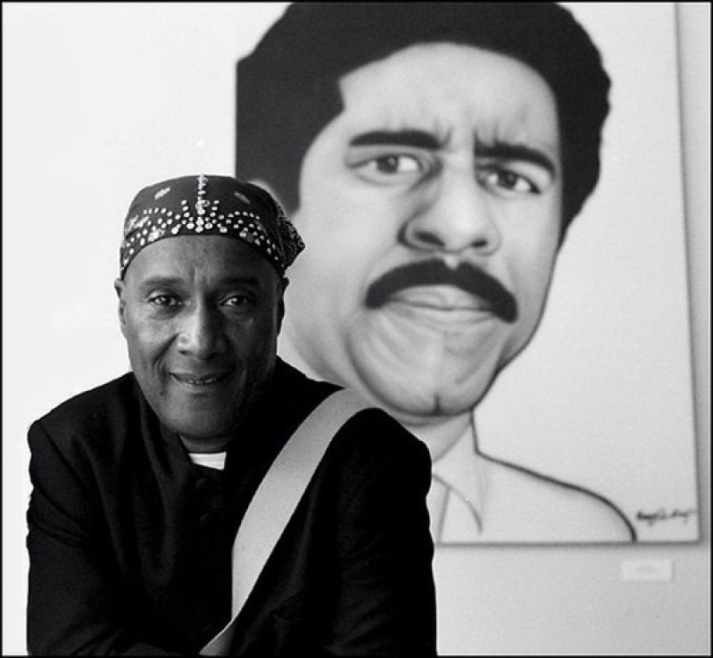 A black and white photo of Paul Mooney: A dark skinned man wearing a bandana over his head, wearing a black coat and white diagonal strap in front, smiling gently at the camera. Behind him is an artistic rendition of Richard Pryor furrowing his brows and pursing his lips.