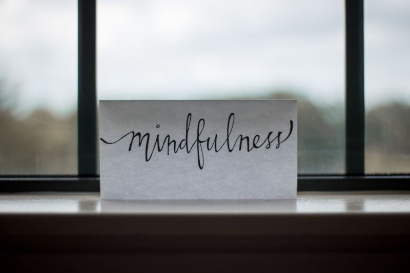 "A slightly translucent piece of paper sits on a window sill, the blurry background of a cloudy landscape behind it. The paper says, ""mindfulness"" in black cursive writing."