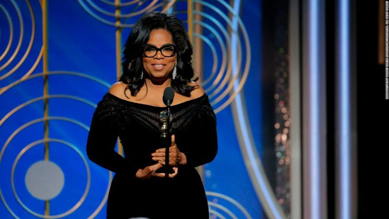 Celebrity Oprah Winfrey stands in front of a blue and silver set on an award show. She's wearing an off the shoulder black dress, her hair is down, and she has thick-rimmed black glasses. She is holding a trophy and speaking into a microphone.